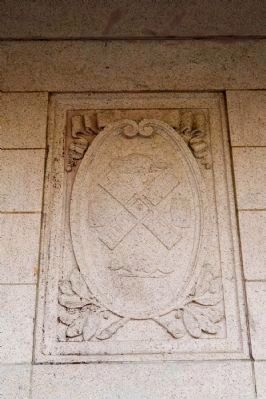 Shield, crest, or perhaps a coat of arms on the museum exterior image. Click for full size.