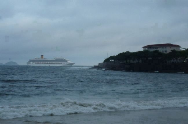 View from Copacabana Beach: a cruise ship off the promontory, departing Guanabara Bay image. Click for full size.