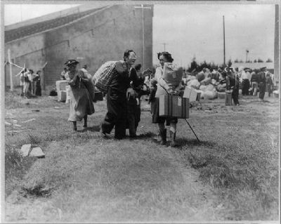 Two Japanese evacuee families meeting at assembly center, Salinas rodeo grounds image. Click for full size.