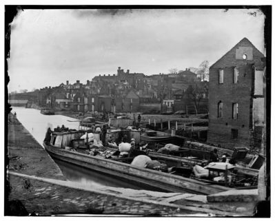 Richmond, Va. Barges with African Americans on the Canal; ruined buildings beyond image. Click for full size.