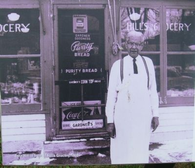 John Hill in front of his grocery store image. Click for full size.
