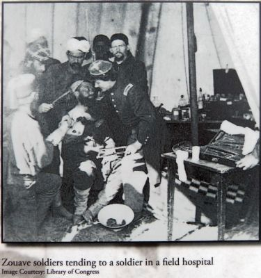 Zouave soldiers tending to a soldier in a field hospital image. Click for full size.