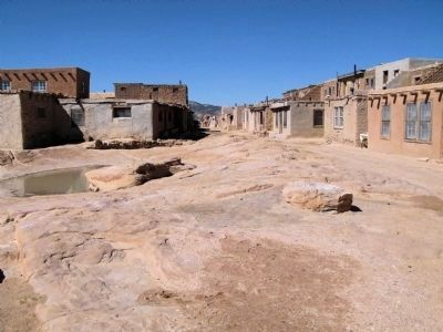 View of street with water cistern or tinaja to left. image. Click for full size.