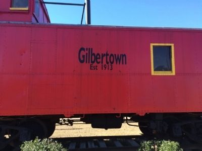 Caboose in Gilbertown near typical oil derrick and pump. image. Click for full size.