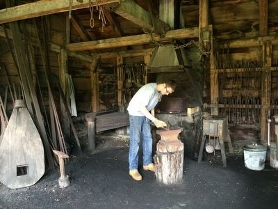 A National Park Service employee working in the blacksmith shop. image. Click for full size.