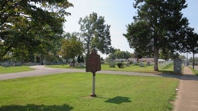 Wide area photo of marker and cemetery graves. image. Click for full size.