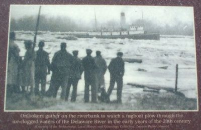 Onlookers gather on the riverbank to watch a tugboat image. Click for full size.