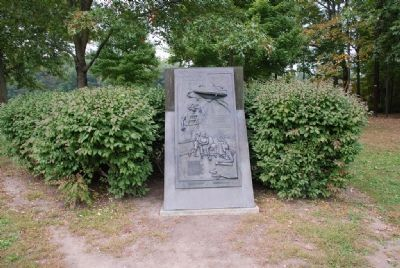 View of marker with bushes and grove of trees visible image. Click for full size.