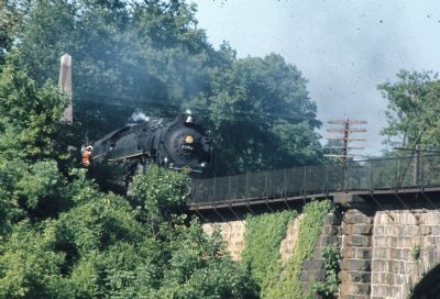 Steam Locomotive Passes Marker, Charges Across Viaduct image. Click for full size.