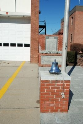 Memorial marker is behind the traditional firehouse bell image. Click for full size.