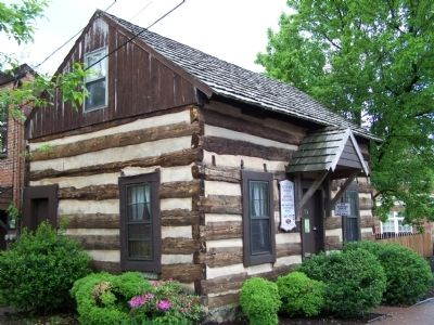 Log cabin adjacent to the marker. image. Click for full size.