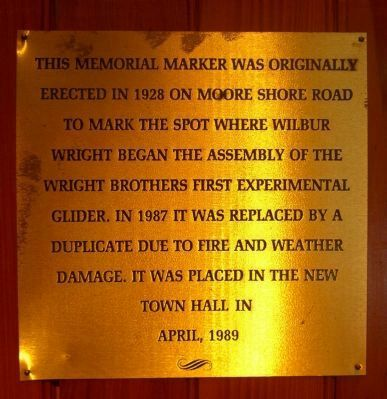 This brass plaque identifies why the memorial was moved inside the town hall image. Click for full size.