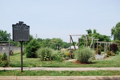 Marker and gardens next to apartments. image. Click for full size.