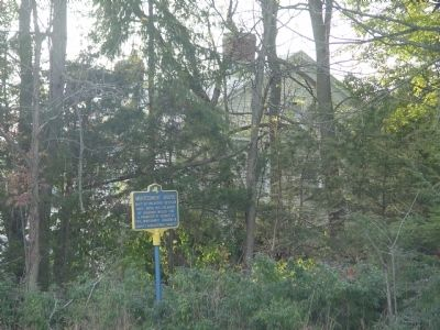 Montgomery House in background behind marker and obscured by vegetation. image. Click for full size.