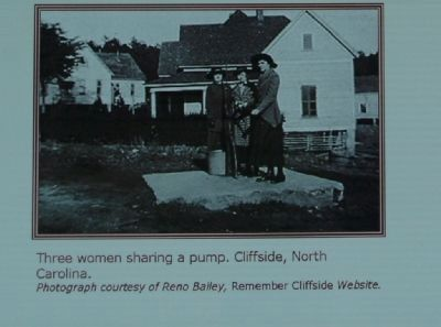Three women sharing a pump, Cliffside, North Carolina. image. Click for full size.
