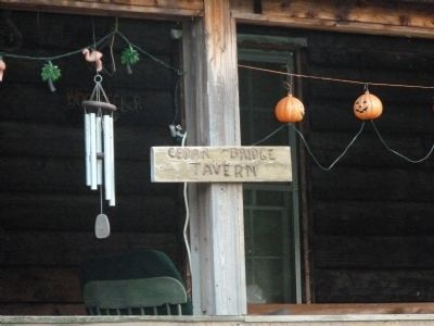 Wooden sign on tavern porch. image. Click for full size.