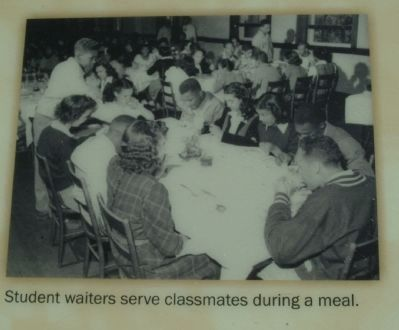 Student waiters serve classmates during a meal. image. Click for full size.
