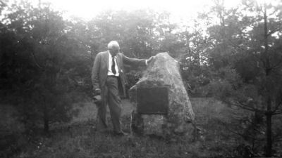 Dr. Schenck standing next to the Biltmore Forest School tablet image. Click for full size.