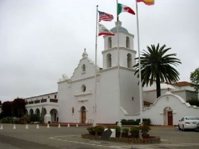 Mission San Luís Rey de Francia & Marker located under the flags. image. Click for full size.