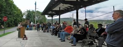 Alan Held speaks to audience gathered under the platform of the 1915 Erie Depot at Chester. image. Click for full size.