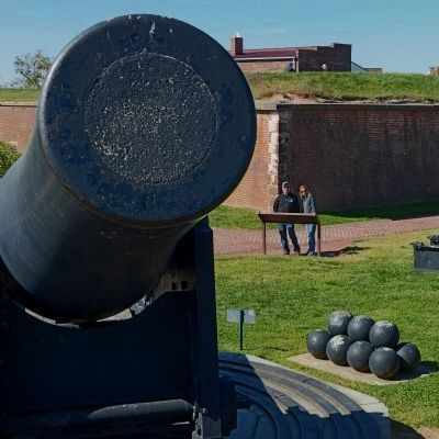 Tourists read the Outer Battery marker behind the muzzle of a 15-inch Rodman gun image. Click for full size.