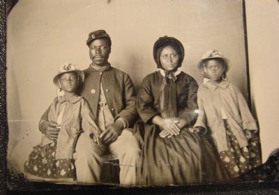 Unidentified African American soldier in Union uniform with wife and two daughters image. Click for full size.