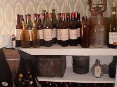 Collection of vintage wine bottles in the Cottage Corners bar image. Click for full size.