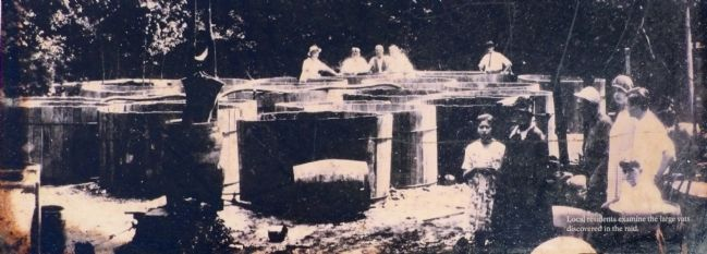 Local Residents examine the large vats discovered in the raid. image. Click for full size.