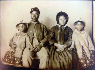 Unidentified African American soldier in Union uniform with wife and two daughters, ca. 1864 image. Click for full size.