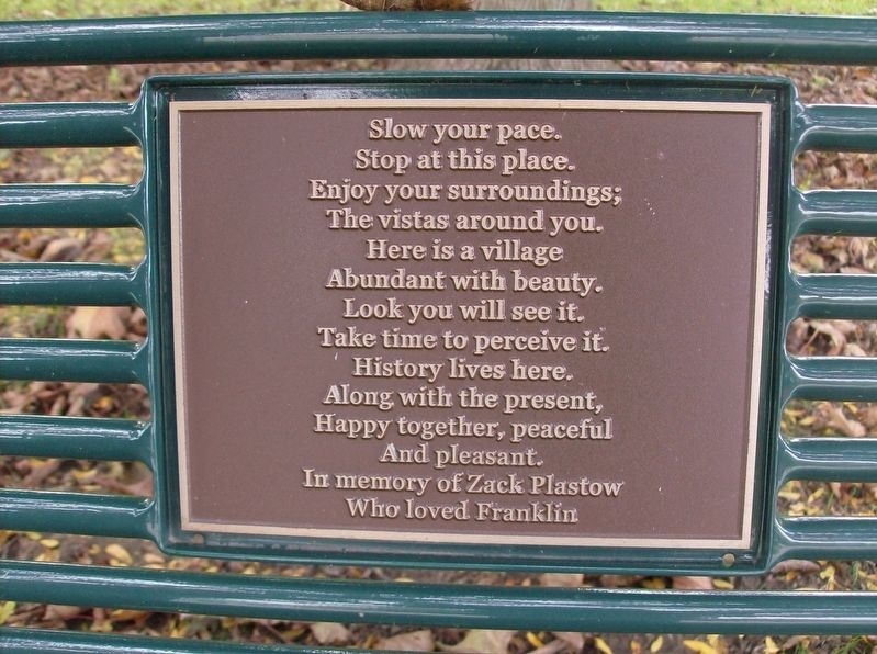 Plaque on park bench next to marker image. Click for full size.