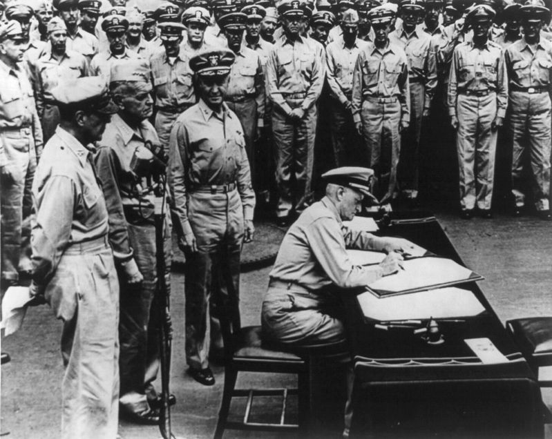 Fleet Adm. Chester W. Nimitz signing surrender document on board the USS Missouri, Sept. 3, 1945 image. Click for full size.