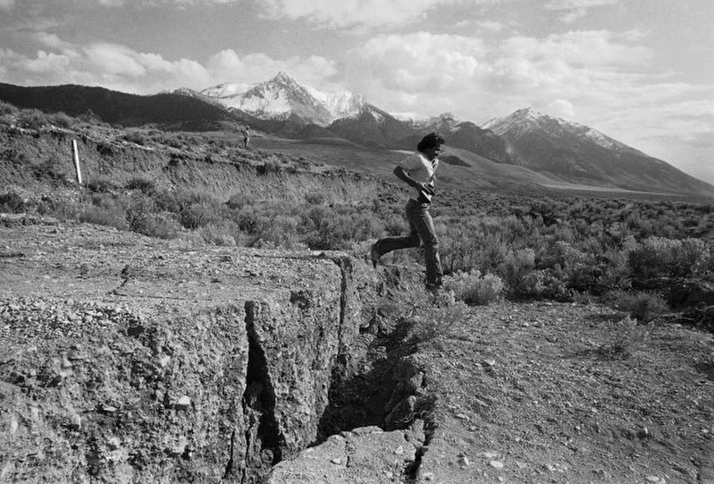 Geologist leaping across the earthquake fault. image. Click for full size.