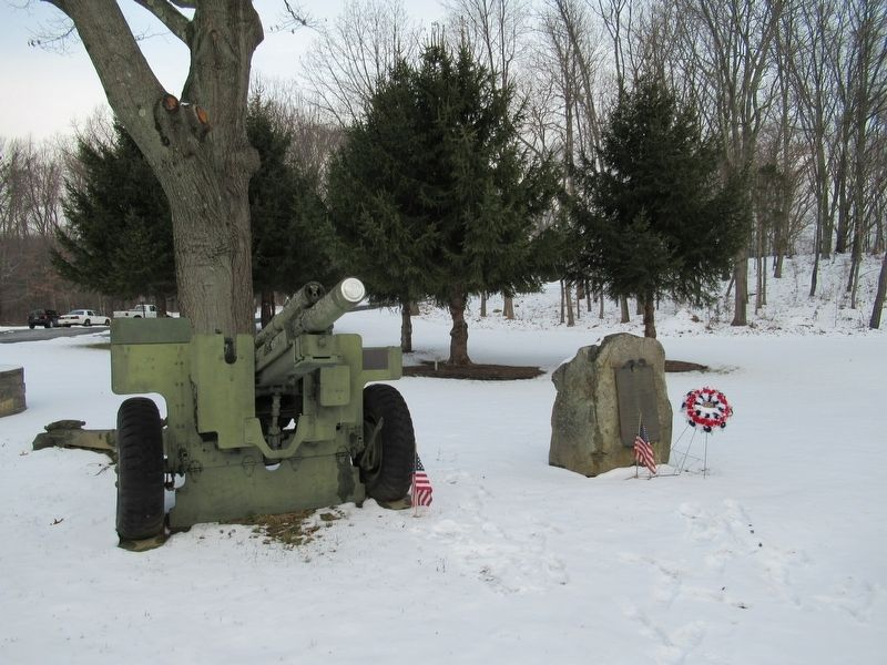A 105mm Howitzer stands next to the Roll of Honor image. Click for full size.