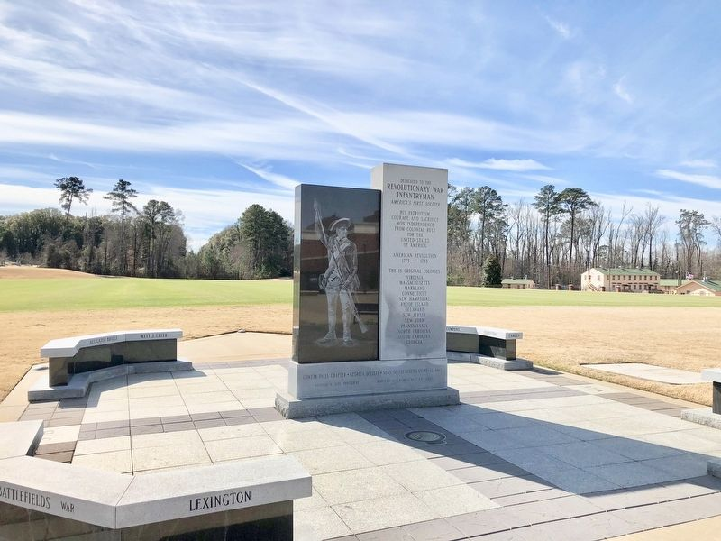 Monument near parade field with WWII Company Street in far background. image. Click for full size.