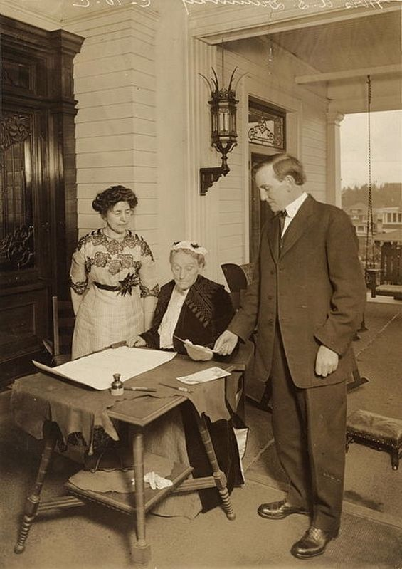 Duniway (seated) with Governor Oswald West, signing the women's suffrage amendment image. Click for full size.