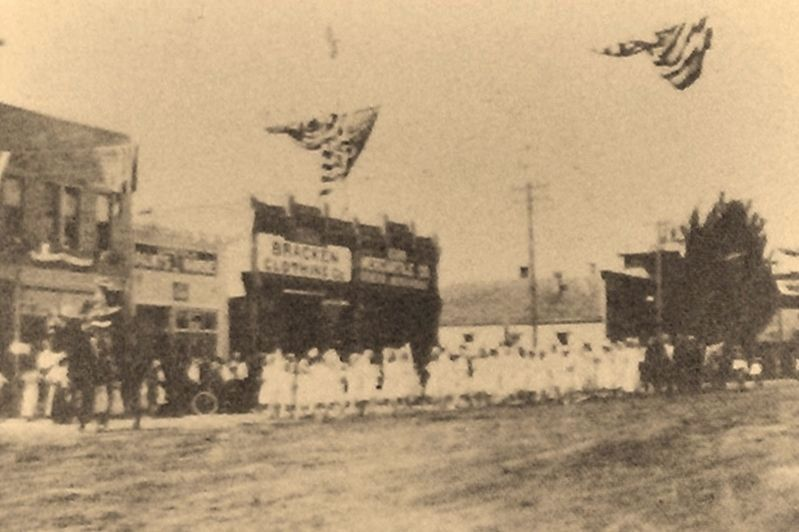 Marker detail: July 4th Parade marching past Acorn Mercantile, 1912 image. Click for full size.