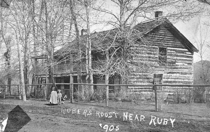 <i>Woman and Boy Stand in Front of the Robbers Roost a Two Story Log Cabin 1905</i> image. Click for full size.