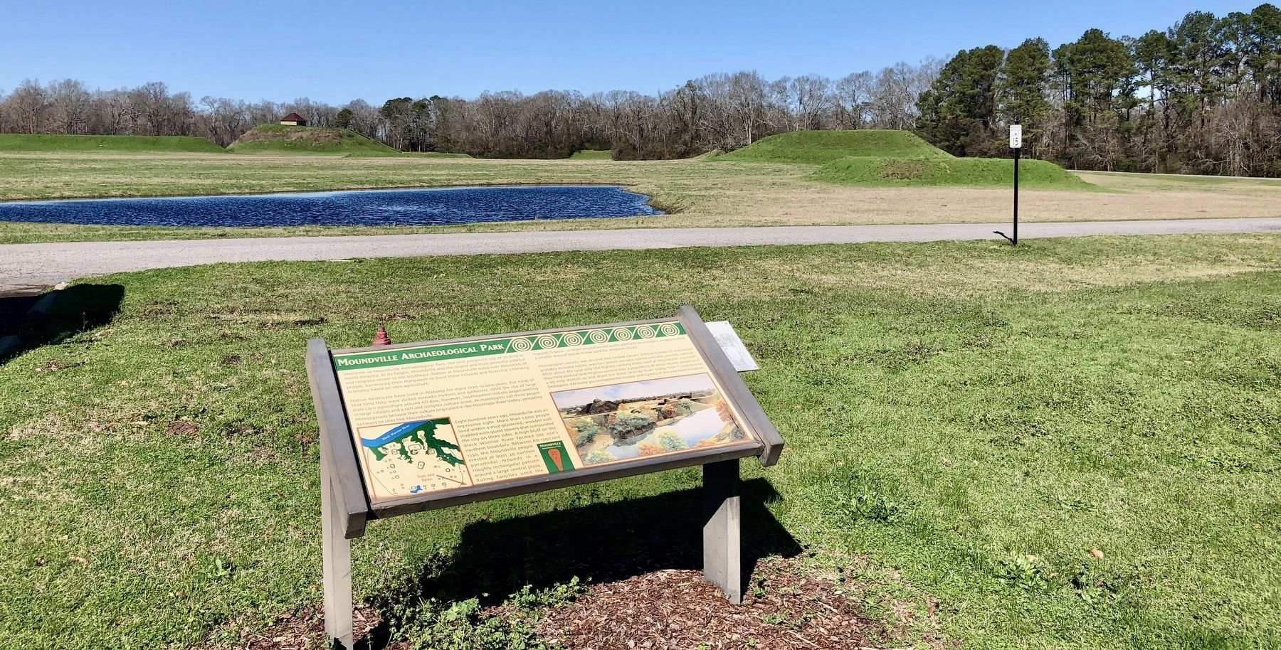 Moundville Archaeological Park Marker with mounds in background. image. Click for full size.