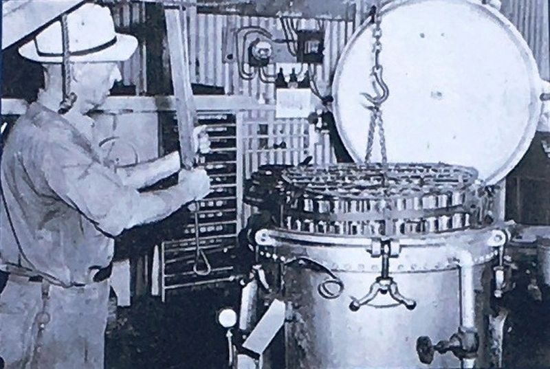 Photo Insert Center: Employee of Saint Marys Canning Company Placing cans in a pressure cooker, 1941 image. Click for full size.