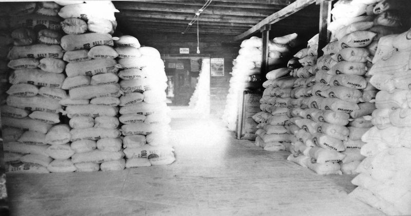 Marker detail: Mill warehouse crowded with local branded sacks awaiting commercial shipment. image. Click for full size.